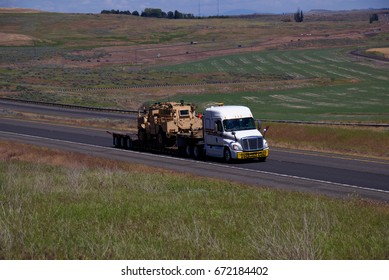 A White semi-Truck pulls a flatbed loaded with Military equipment down a rural US highway. June 20th, 2017 Oregon, USA