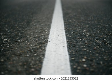 A white separation route on the gray asphalt
