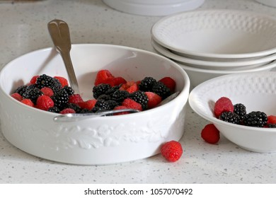 White serving bowl filled with fresh blackberries and fresh raspberries along with several small bowls ready to be filled.