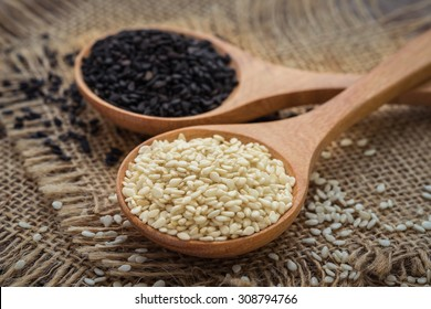 White sesame and black sesame seed on wooden spoon