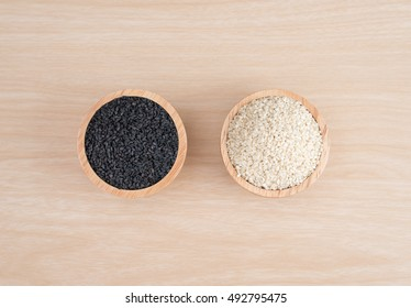 White sesame and black sesame seed on wooden background. Top view.