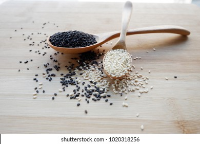 White sesame seeds and black sesame seeds are in a wooden spoon.