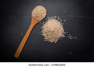 White sesame seeds in spoon on black granite backgroud