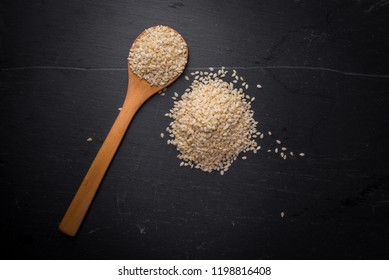 White sesame seeds in spoon on black granite backgroud