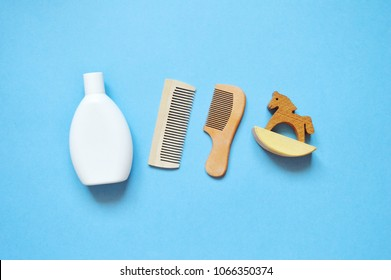 White shampoo bottle, two wooden combs and rocking horse toy on a blue background. Flat lay photo hair care items