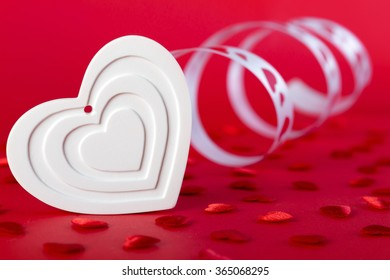 White shape heart with ribbon and red hearts on red background. Valentines day concept.