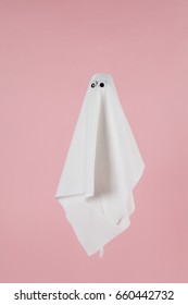 white sheet ghost with doll's eyes isolated on a pink background. Studio still life minimal photography