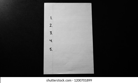 A white sheet of lined paper placed on a black table surface. Numbered list 1. 2. 3. 4. 5. to be filled out.