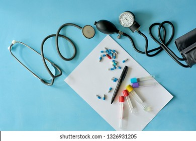White sheet paper with black pen and colored pills, capsules, phonendoscope stethoscope, sphygmomanometer, vacuum venipuncture test tubes on blue background with copy space for text. Medicine consept.