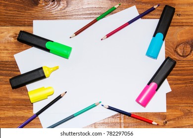 A white sheet of paper lay on a wooden table, near , pencils, markers, pens . The view from the top.