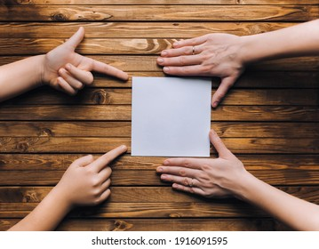 A white sheet of paper lies between the hands of a young girl and a little girl. The knotted fingers point to the empty space of the cardboard. Layout, mockup concept with copy space.
