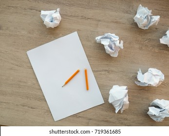a white sheet of paper near some crumpled paper, a broken pencil, a concept in search of ideas, insights, creativity, study, memorize