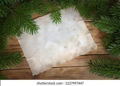 white sheet of paper on wood with fir branches