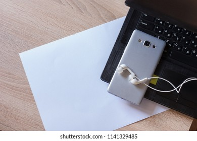 white sheet of paper on a wooden table next to a laptop and phone