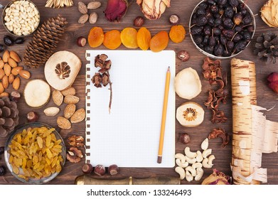White sheet of paper with a pencil in an environment of nuts and fruits
