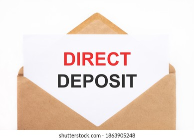 A white sheet with the text direct deposit lies in an open craft envelope on a white background with copy space. Business concept image