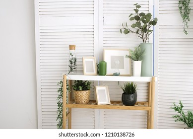 white shelf with hourglass, candle, frame. place for text