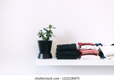 White shelf with neat piles of clothes and a plant. Organization of cozy home space. Matte toned