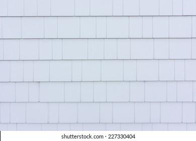 White shingle style siding on a house near the coast