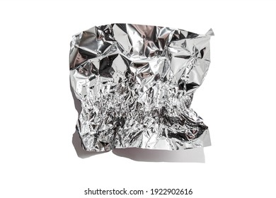 White shiny aluminum foil wrap without chocolate candy on a white background. Texture of used crumpled aluminium food foil.