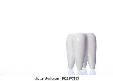 White shiny decorative tooth. Close up of tooth-shaped holder for toothbrushes isolated on white background copy space. dental cabinet furniture. Advertising of dentistry services