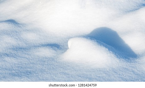 white shiny fluffy snow lies a hill on the ground outside in cold winter