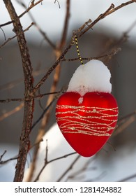 white shiny fluffy snow on a red toy heart with sparkles and tree branches