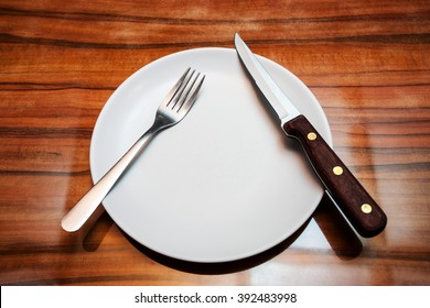 White shiny plate with folk and knife