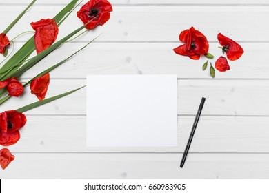 White ship deck tabletop scene with poppies and a blank white paper