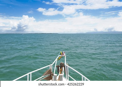 White ship prow moving toward island in the green sea on sunny day with blue sky and white clouds, local boat in ocean