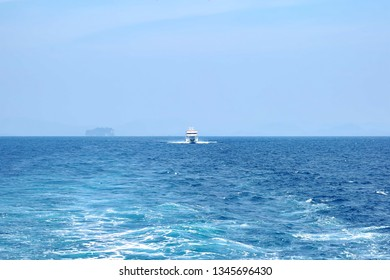 The white ship pursues another ship at sea. Clear sunny day, blue sky