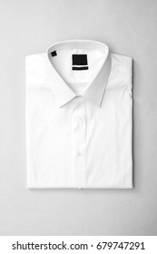 White shirt with blank label on isolated background, top view