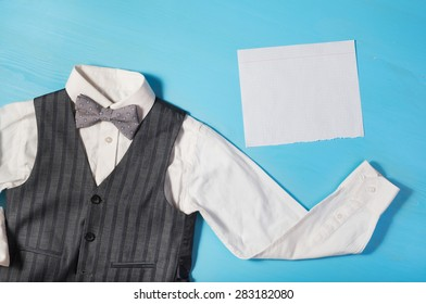 white shirt, gray vest, bow tie and a sheet of paper for text  on a bright blue background, the concept of the festival, celebrations, ceremonies happy Father's Day, Happy Birthday Dad