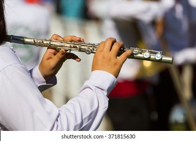white shirt musician in marching band playing metal flute on band background