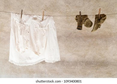 A white shirt and a pair of knitted woolen socks hanging on a laundry rope with wooden clothespins