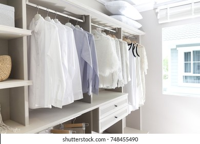 white shirts and blouses hanging in closet