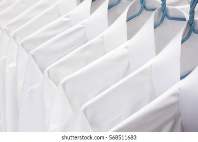 White shirts hanging on rack in a row, Selective focus