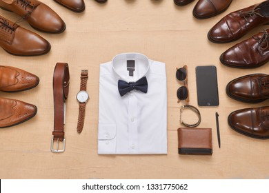 white shirt,watch, brown shoes, brown purse,cell phone, sunglasses belt, -wooden background