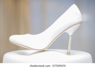 The white Shoe of the bride is placed on a stand.