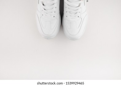 White shoes isolated on white background. Closeup photography of snickers, place for text