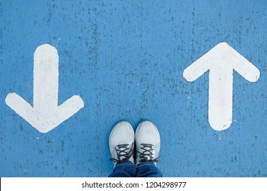 White shoes standing on blue concrete floor making decision which way to go - forward or backward.