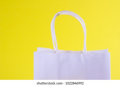white shopping bag on yellow background with space for your logo or text