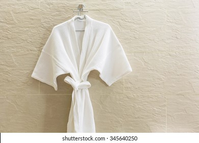 White shower gown  hanged in the bathroom with stone tiles wall background.