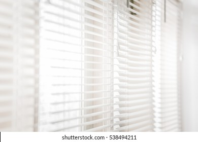 White shutters on windows with bright sunlight shining through.