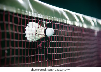 White SHUTTLECOCK hold on the red badminton net at Badminton court background.