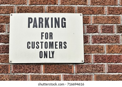 White sign with black letters on a brick wall for customer parking only