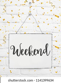 White sign board with text happy weekend with golden confetti on white brick background