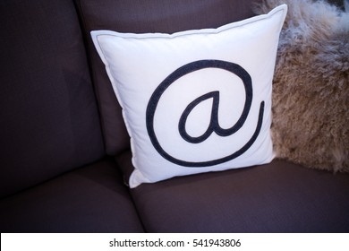 White at sign pillow on brown sofa