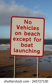 A white sign with the words 'no vehicles on beach except for boat launching' written in red with a beach in the background.