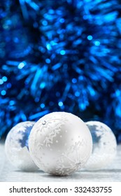 White and silver christmas balls on dark blue bokeh background with space for text. Merry christmas card. Xmas. New Year